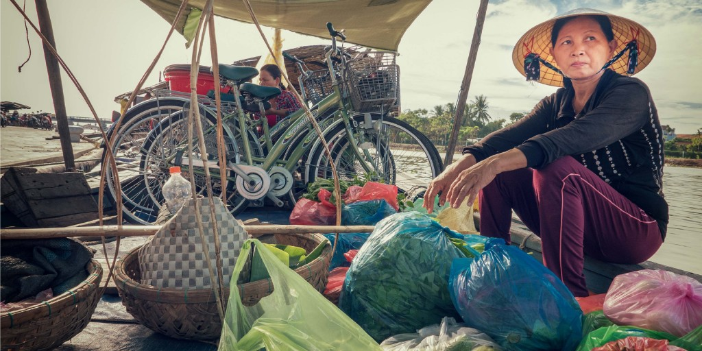 A Vietnamese woman travels on a boat crowded with produce