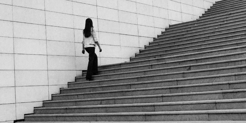A black and white image of a young woman walking up some steps.
