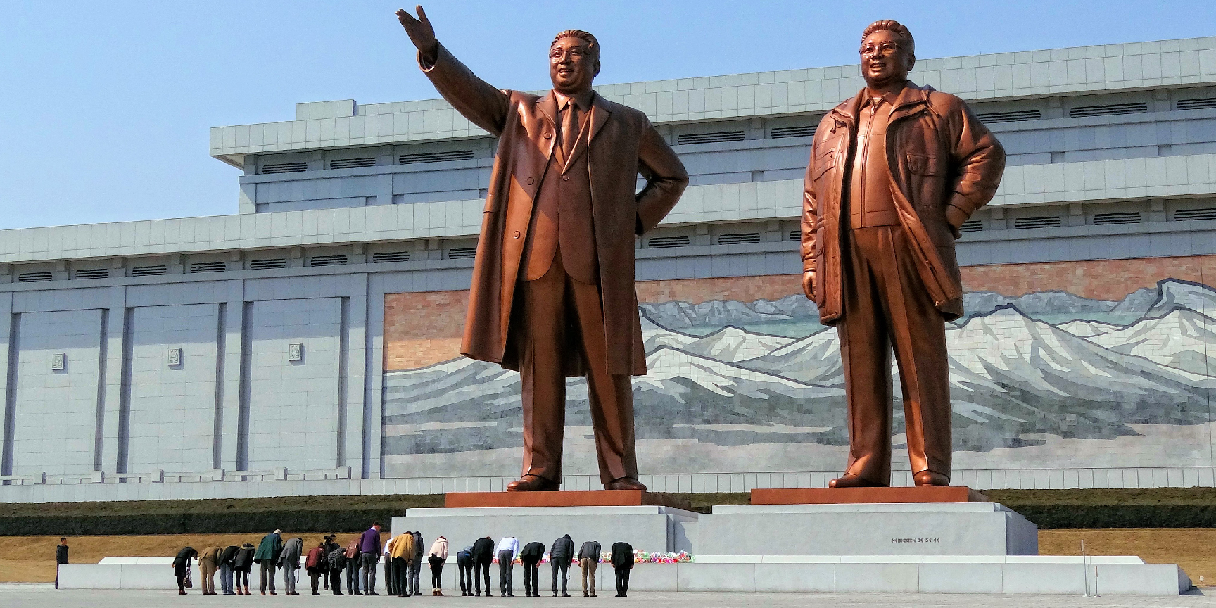 People bow before the Mansudae Grand Monument which depicts Kim Il Sung and Kim Jong-il