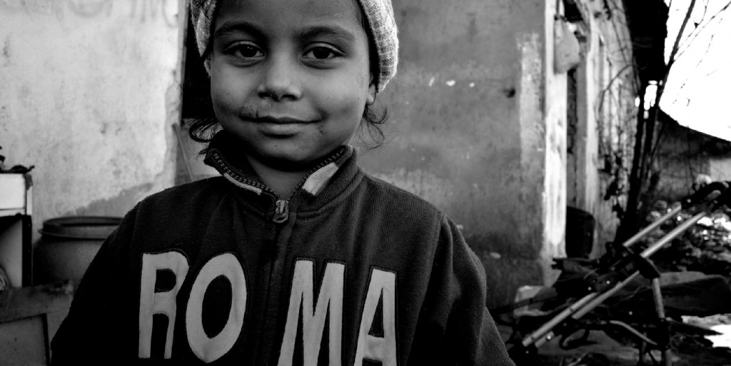 "A young Roma girl in a sweater which reads ""ROMA"""
