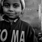 """A young Roma girl in a sweater which reads """"ROMA"""""""