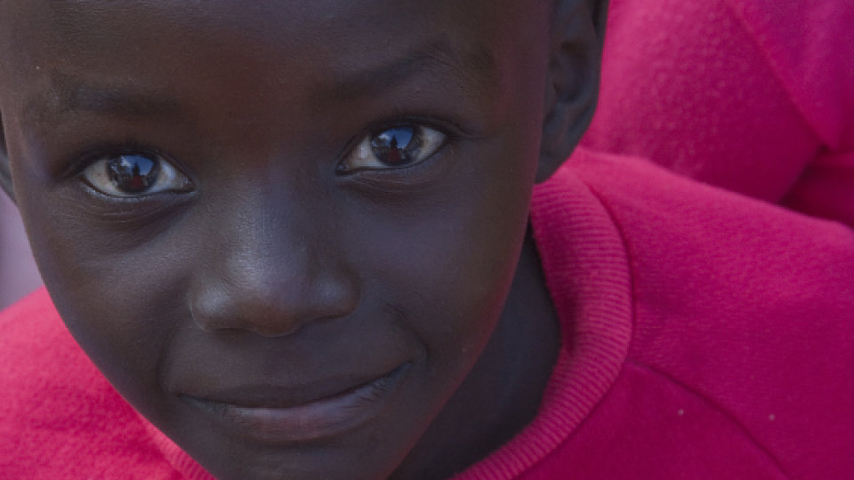 A young South African boy smiles at the camera