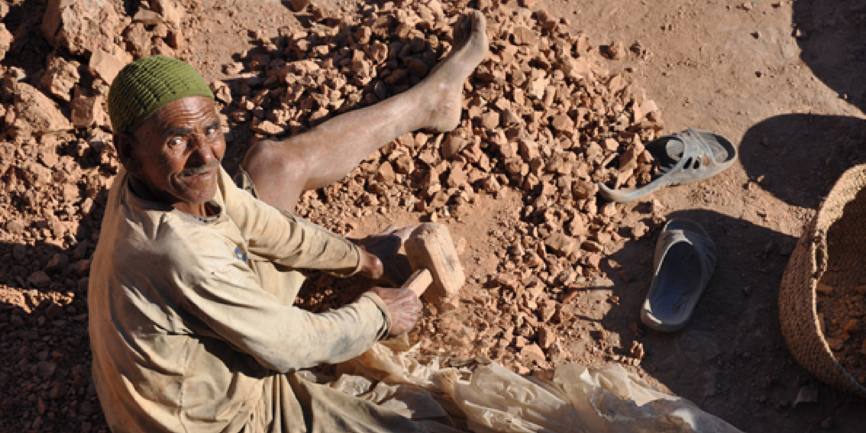 A North African man breaks up rocks with a mallet
