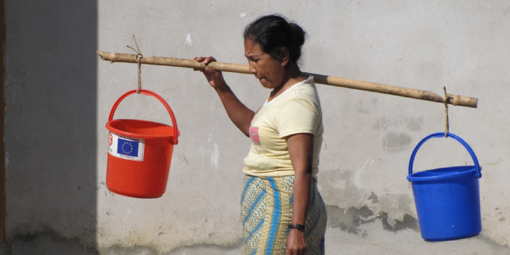 A woman carrying buckets on a pole
