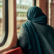 A woman in the Middle East looks out of a train window.